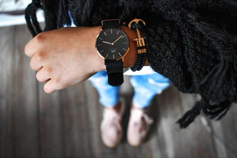 Women in black sweater looking down at her watch