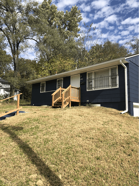 navy home with a well kept yard and new walkway