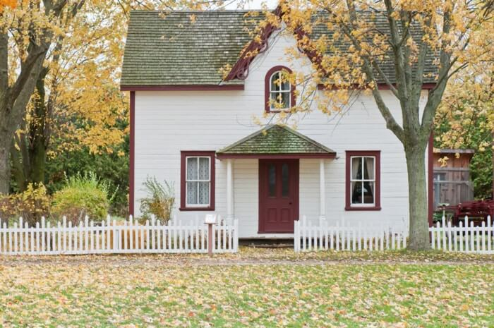 a white house with red door under maple trees