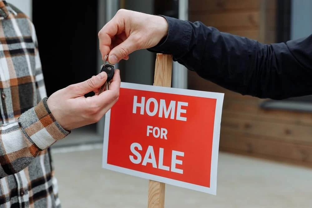 a red and white home for sale sign